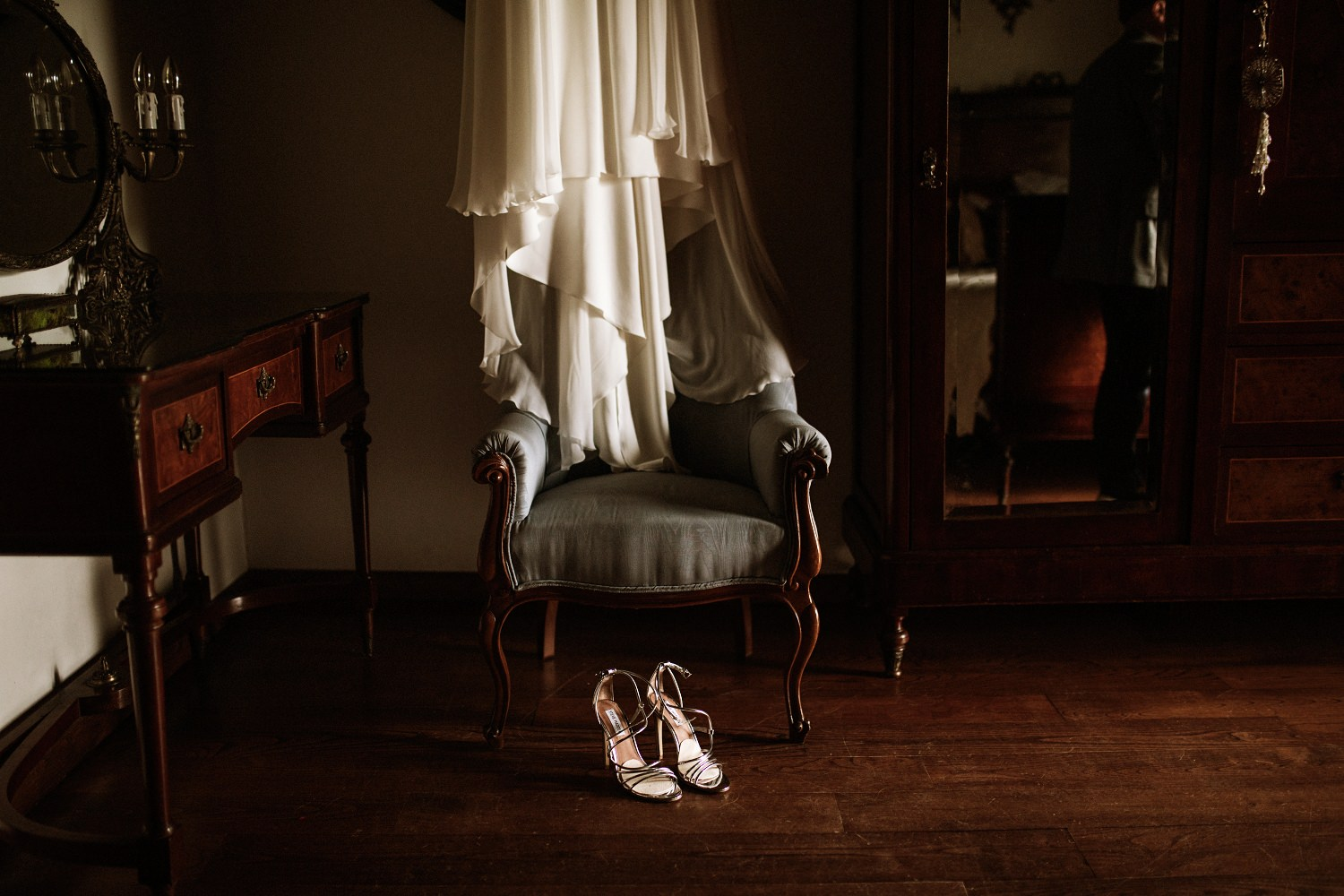 A beautiful portrait of a wedding gown draped over an antique chair