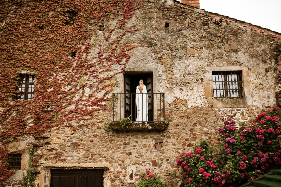 Bride stands outside balcony before her wedding in Asturias Spain