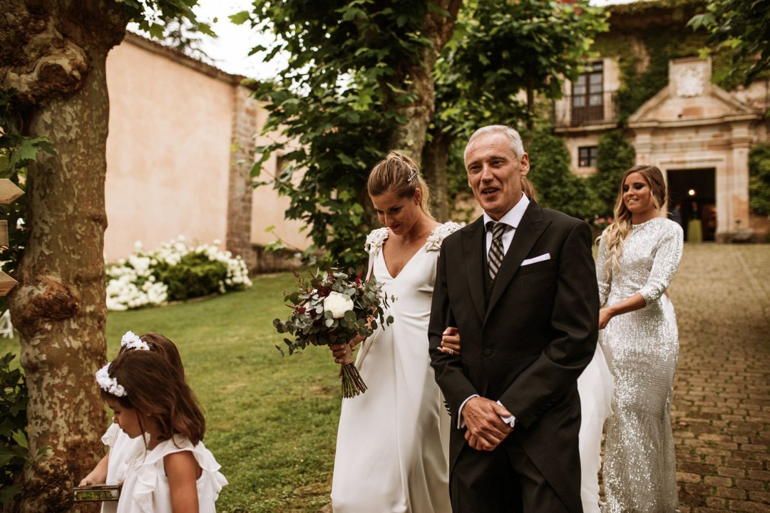 Bride and her father walk towards the church for the wedding ceremony