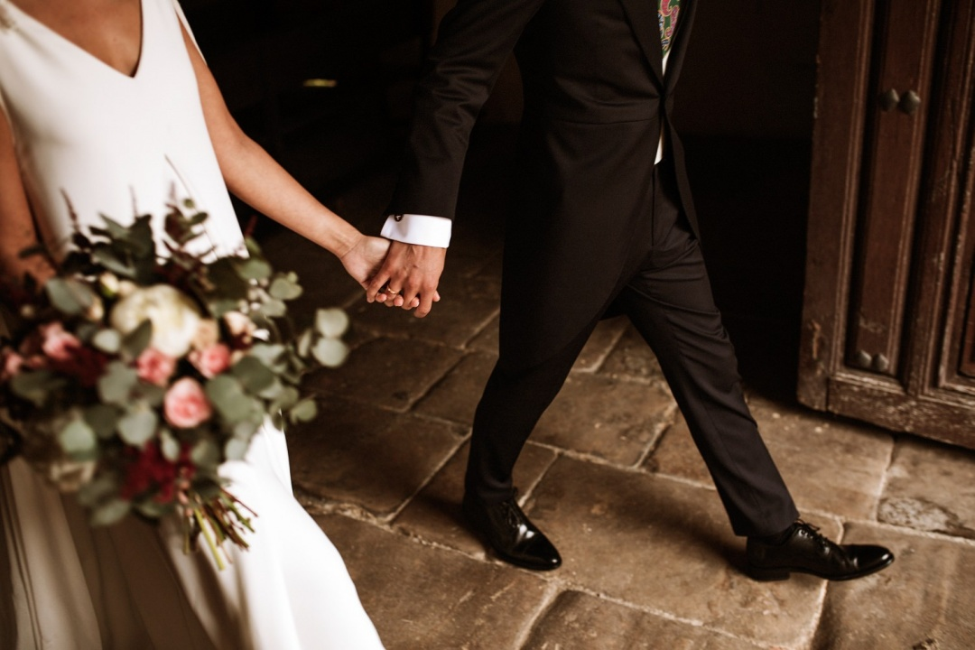 Bride and groom's hands holding as they exit their wedding ceremony