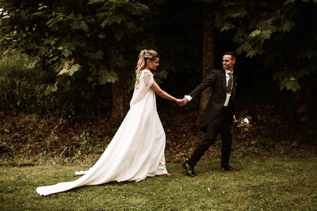 Bride and groom hold hands after their wedding in Asturias. Groom leads bride walking