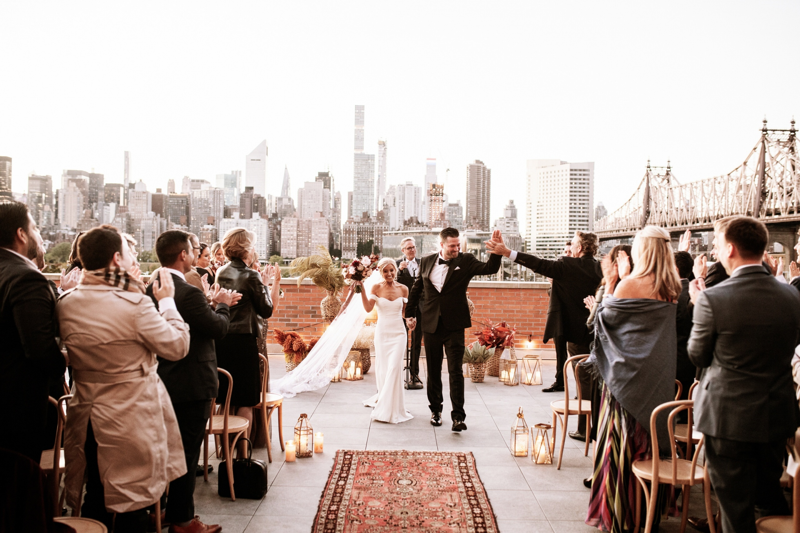 A newly married couple happily walks down the aisle with NYC skyline in the background