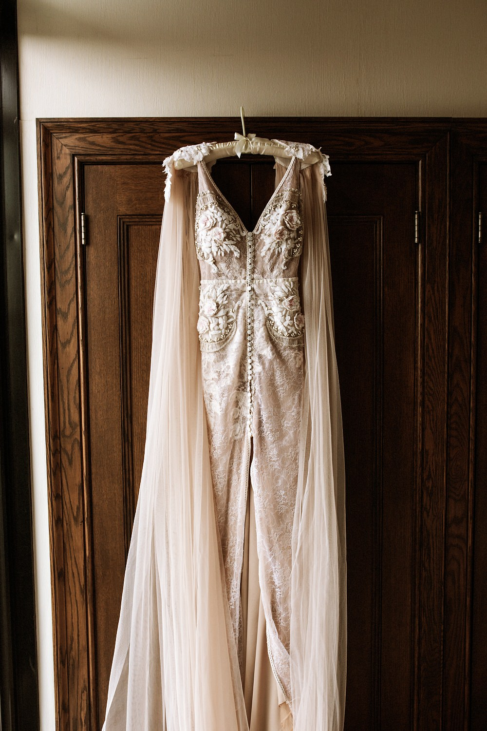 Ludlow Hotel Wedding - A flowing wedding dress hangs from close door by the window
