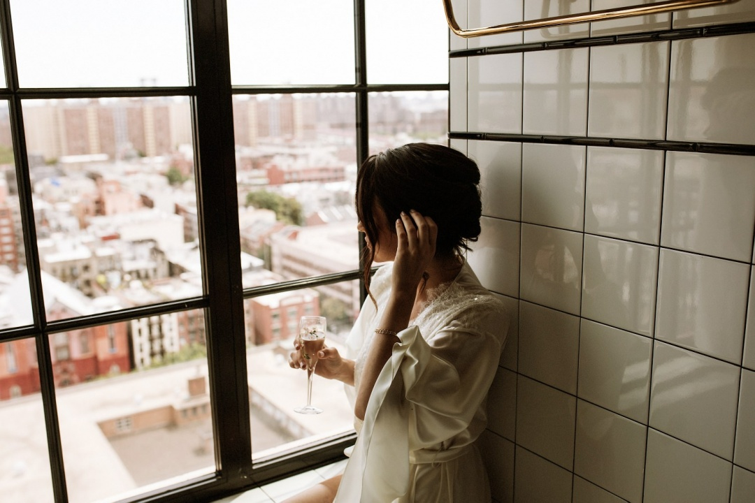 Ludlow Hotel Wedding - Bride drinks a glass of champagne as she looks out the window