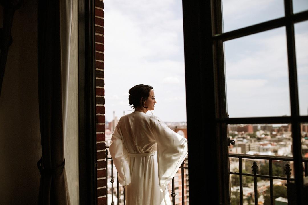 Ludlow Hotel Wedding - New York - Bride on the balcony of her hotel overlooking Manhattan