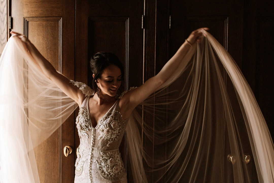 Ludlow Hotel Wedding - Bride raises her arms to show the flowing lace veil of the wedding dress