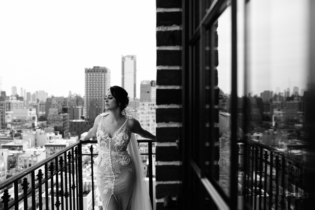 Ludlow Hotel Wedding - Bride poses on the balcony with the NYC skyline as a backdrop