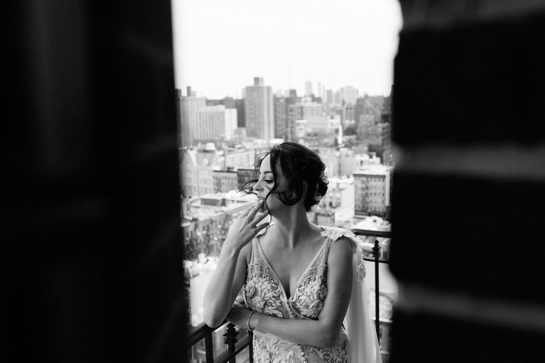 Ludlow Hotel Wedding - A classic black and white photo of the bride on the balcony of the Ludlow overlooking the Manhattan skyline