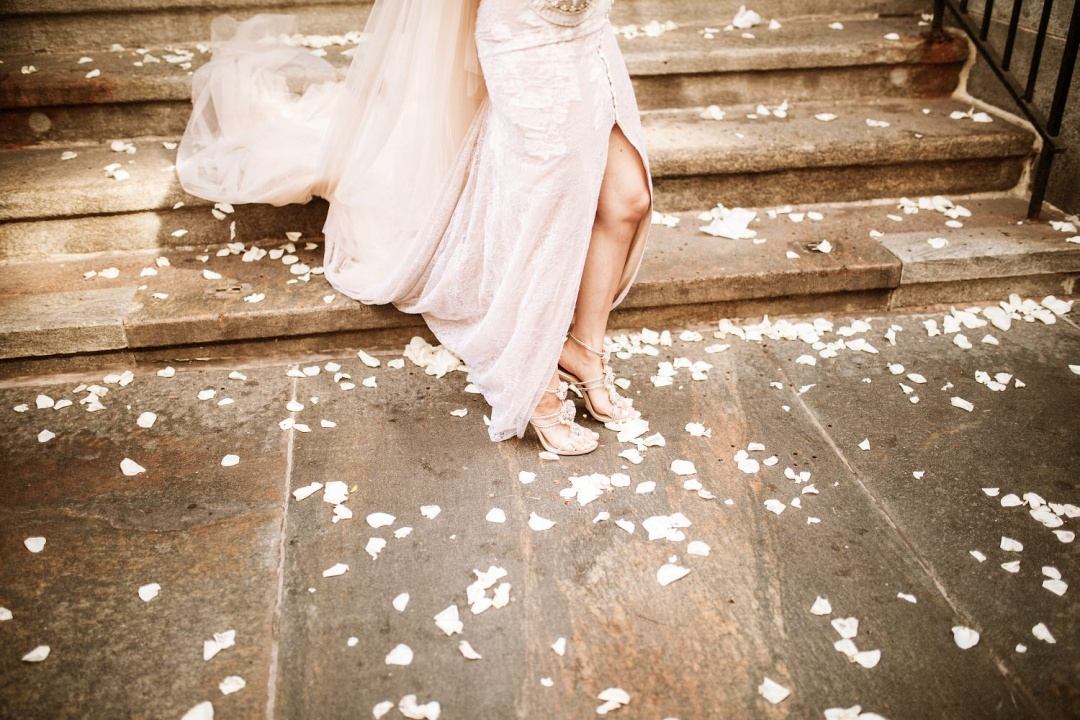 Ludlow Hotel Wedding - Bride walks on rose petals as she exits the church