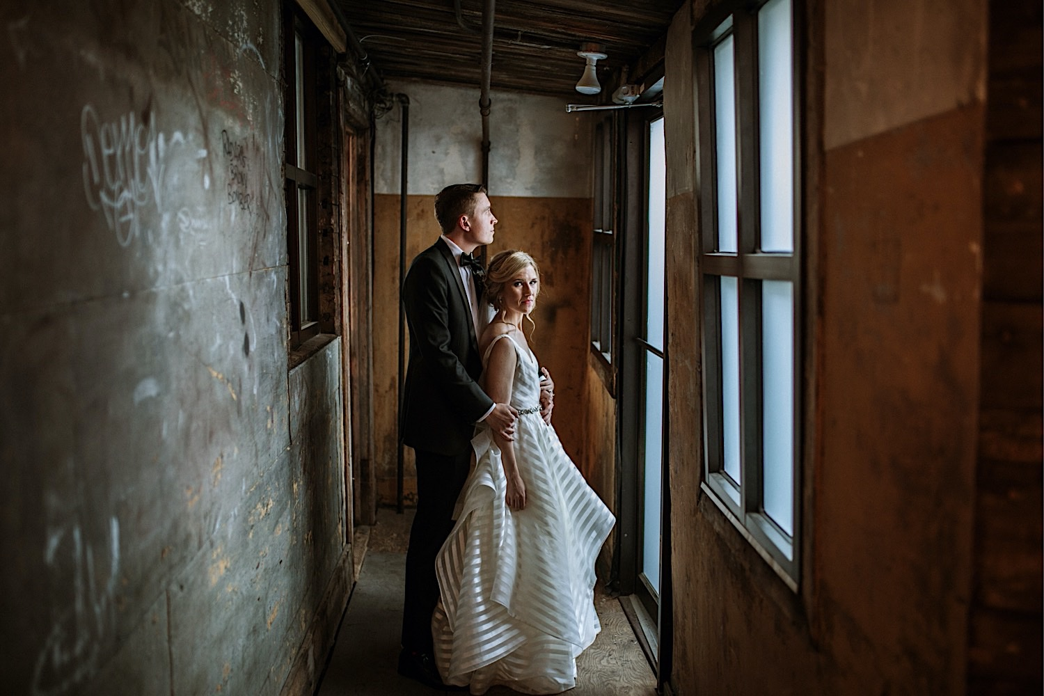 Wedding Photography at Greenpoint Loft - Bride looks at camera as groom holds her from behind