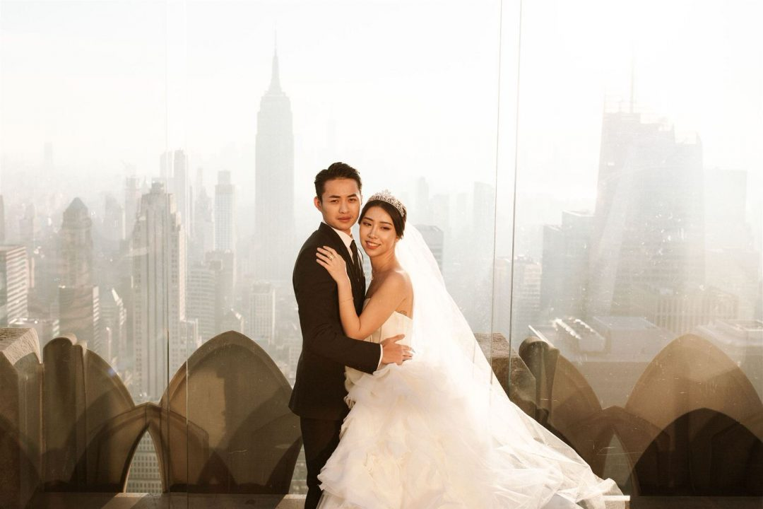 NYC Pre Wedding Photography Bride and groom hold each other and smile at the camera during sunset at the top of the rock New York City