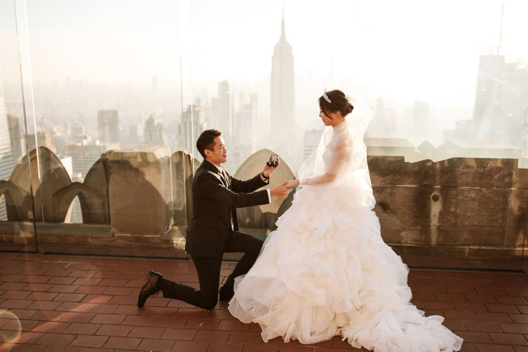 Grooming yours and presents wedding ring to bride with Empire State in the background at sunset. Top of the rock New York City