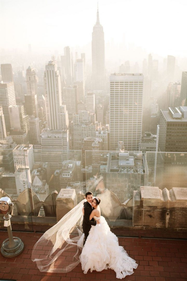 NYC Pre Wedding Photography Bride and groom stand at Sunset with New York skyline in the background. Top of the rock New York City