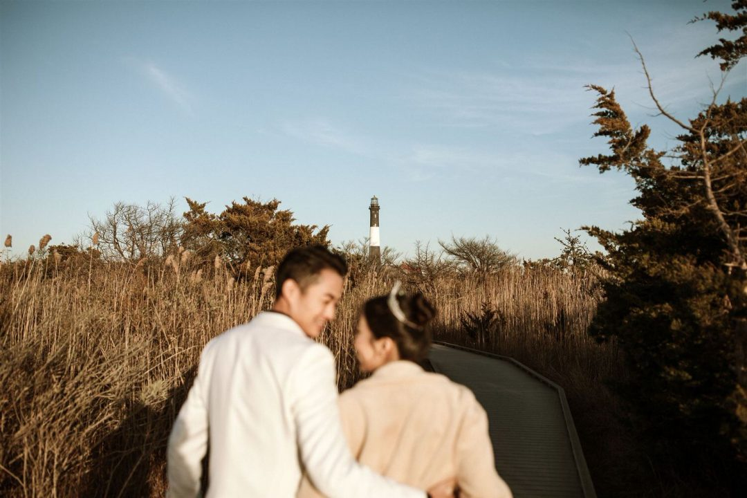 Bride and groom walk towards fire Island lighthouse at Sunset