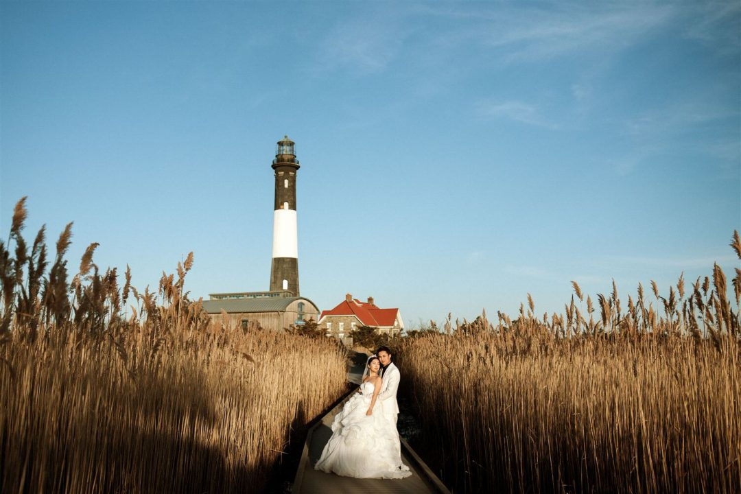 Bride and groom pose with fire Island lighthouse in the background at Sunset