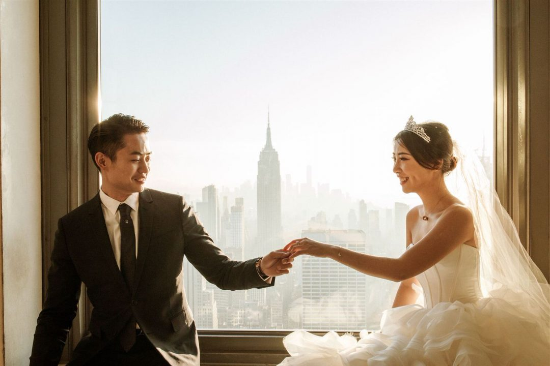 NYC Pre Wedding Photo Bride and groom hold hands with the Empire State in the background at the top of the rock