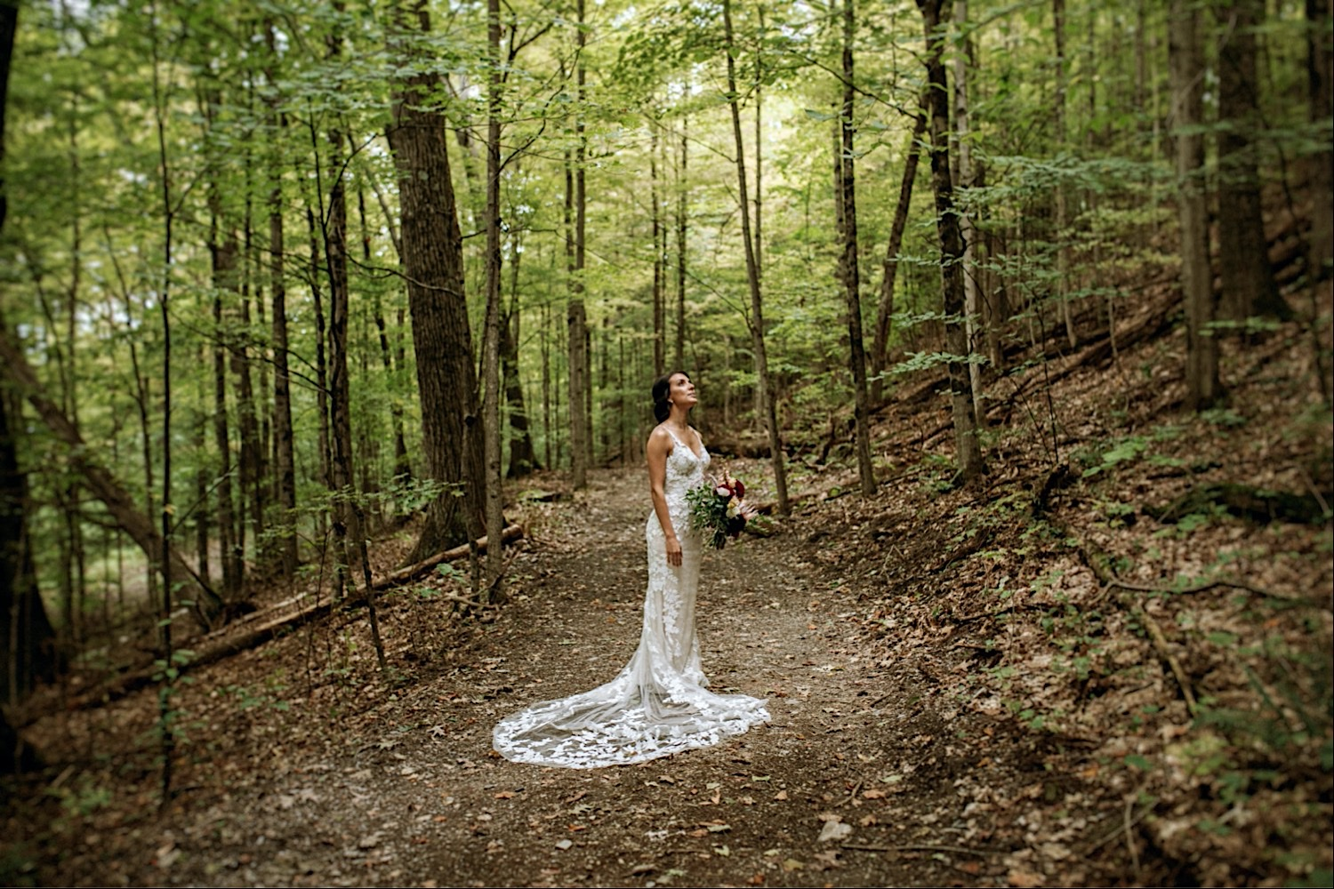 Bomoseen Lodge Wedding - Bride looks upwards towards the light as she stands in her wedding dress in the forest