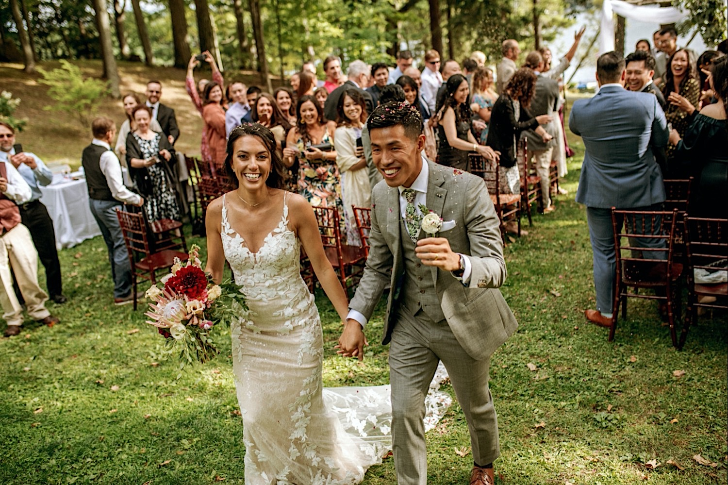 Bomoseen Lodge Wedding - A smiling bride and groom exit the ceremony surrounded by their guests