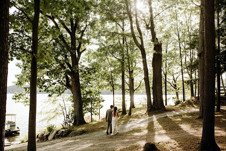 Bomoseen Lodge Wedding - Bride and groom take a stroll on Neshobe Island amongst the trees