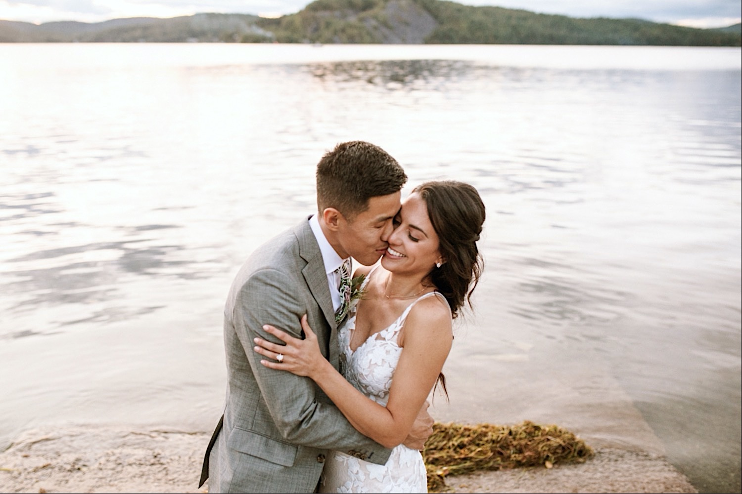 Bomoseen Lodge Wedding - Bride and Groom hold each other closely at sunset on the lake shore