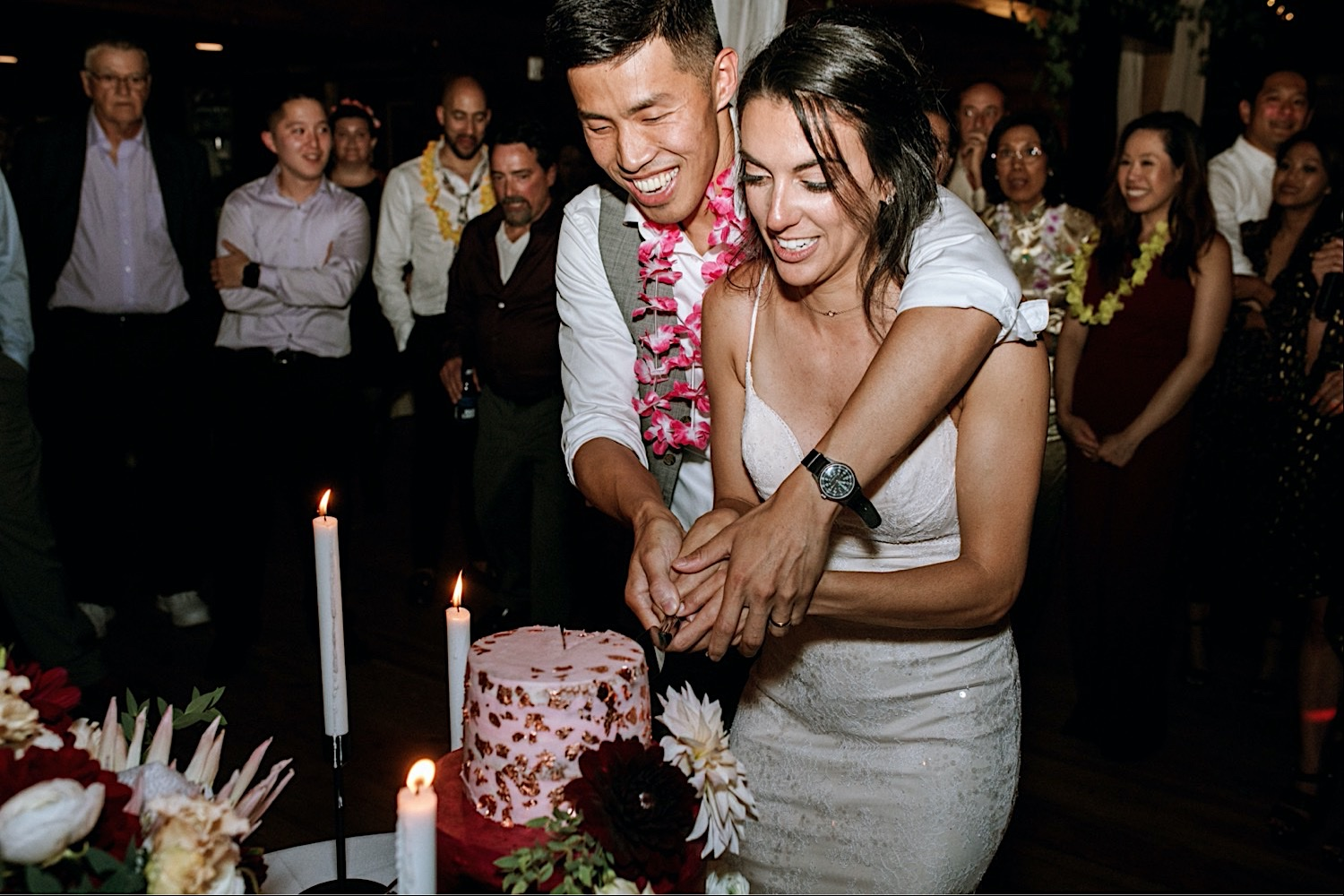 Bomoseen Lodge Wedding - Bride and Groom cut the cake wearing a lei