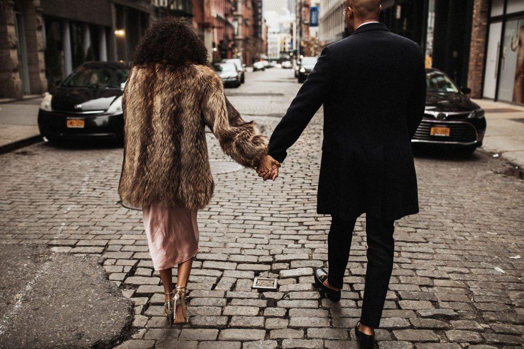 Couple walking down a cobblestone street in SoHo New York City