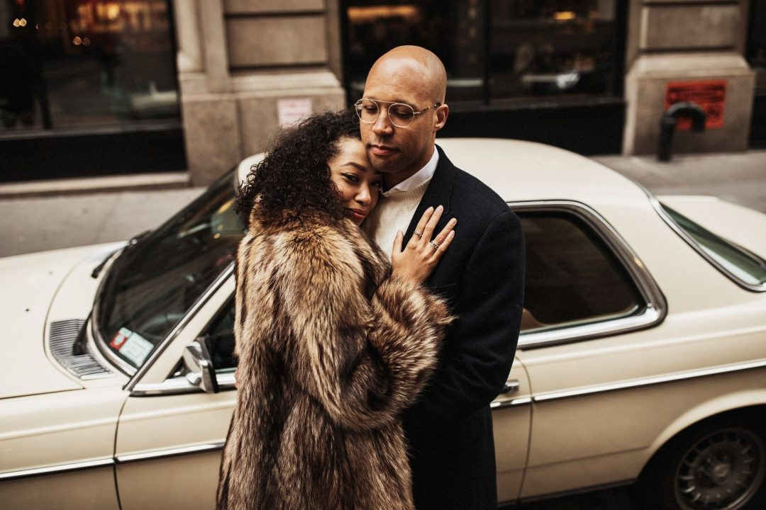 Stylish couple posing next to a vintage Mercedes car in SoHo NYC for an engagement session