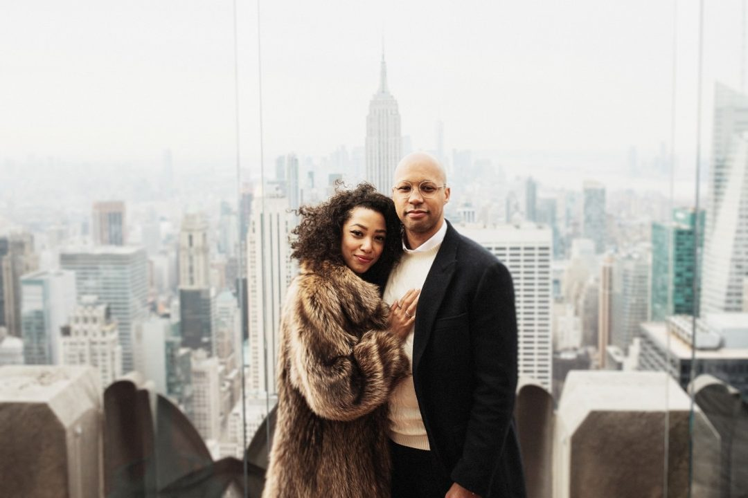 SoHo and Top of the Rock Engagement Session - a couple stands together with the Empire State in the Background