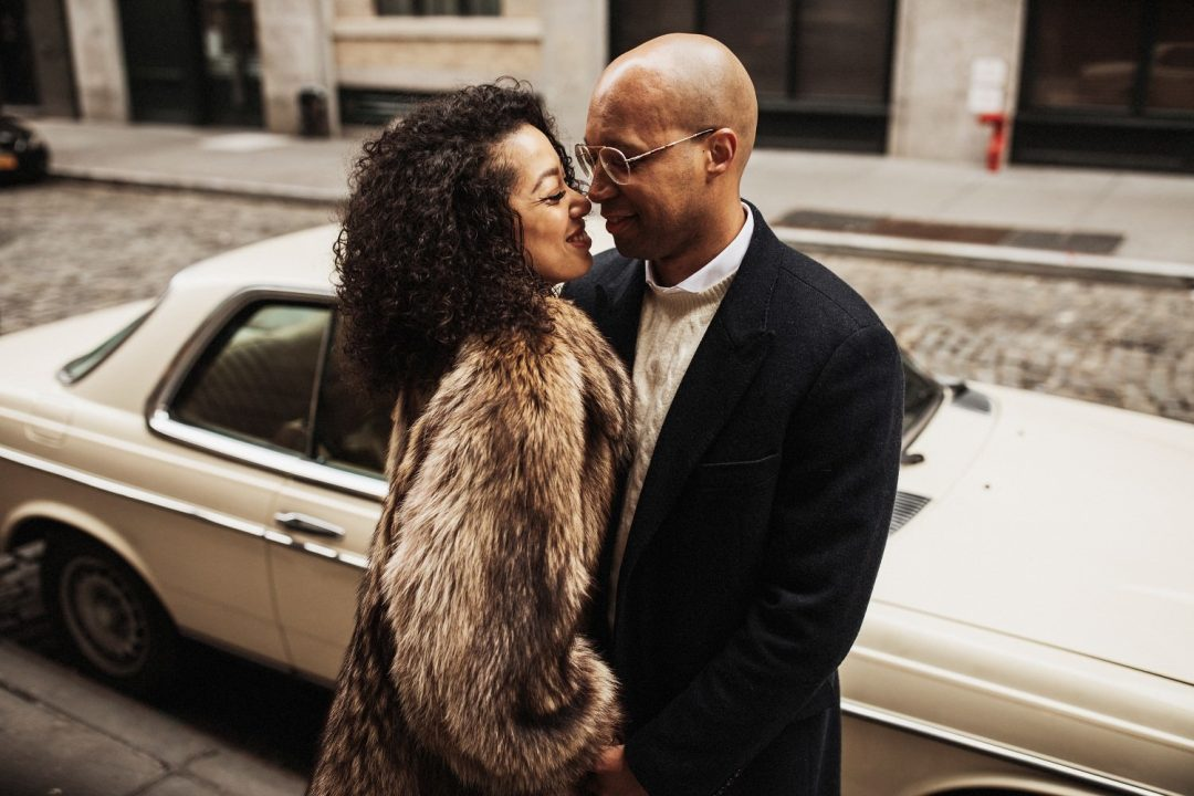 Stylish couple holding each other and smiling next to a vintage Mercedes car in SoHo NYC for an engagement session