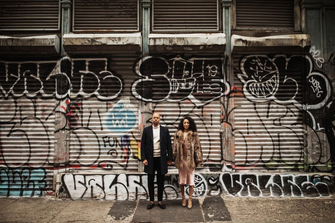 Hand in hand, a stylish couple stands for the camera in their SoHo engagement photo shoot