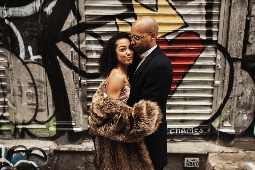 Standing together against a wall of graffiti. Engagement Session in SoHo NYC