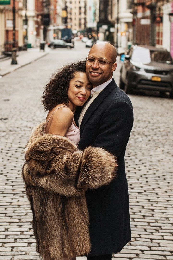 Couple smiles at the camera as they stand in the middle of a cobblestone street in New York city for their SoHo Engagement Session