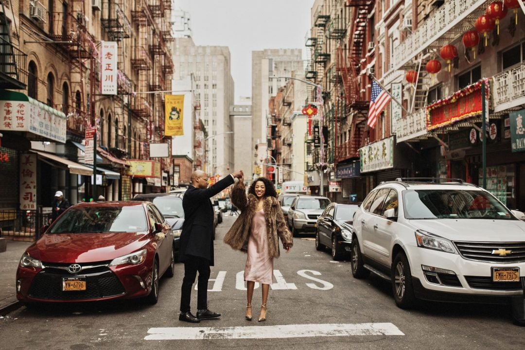 Couple dancing together in the middle of the street in Chinatown New York City. Engagement Session and Shoot