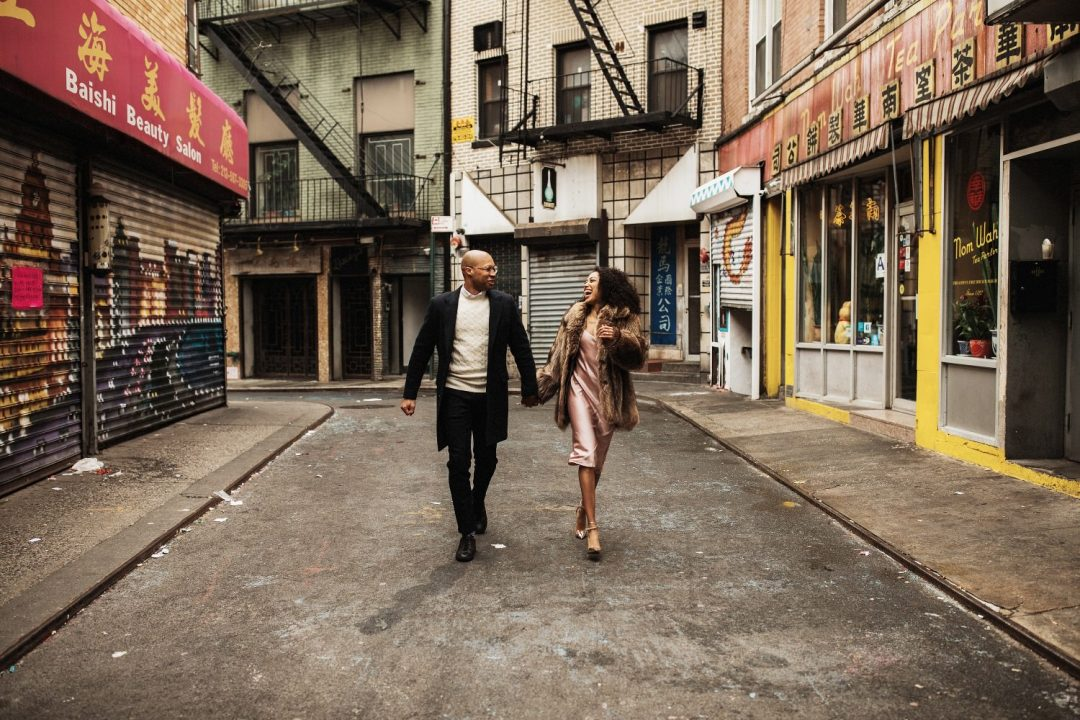 Couple running along Pell Street Chinatown for their Engagement session