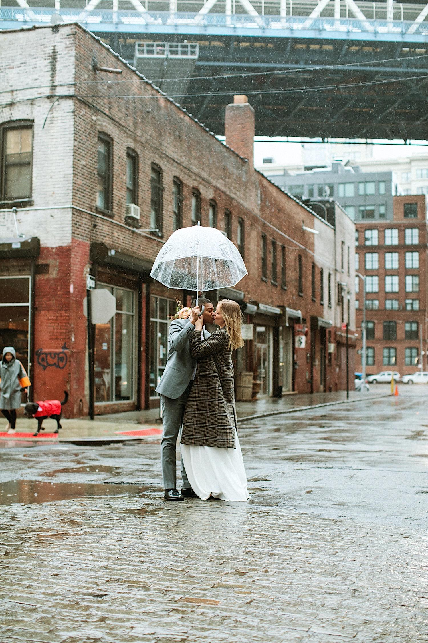 DUMBO Wedding Photography - A couple kisses in DUMBO NYC with an umbrella in the rain