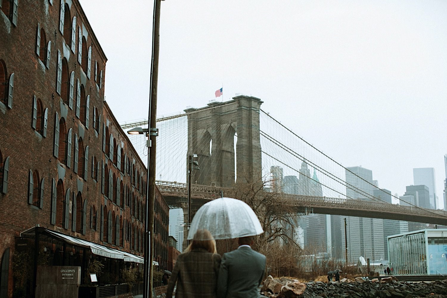 Wedding Photography - a couple walks toward the Brooklyn Bridge in DUMBO under their umbrella