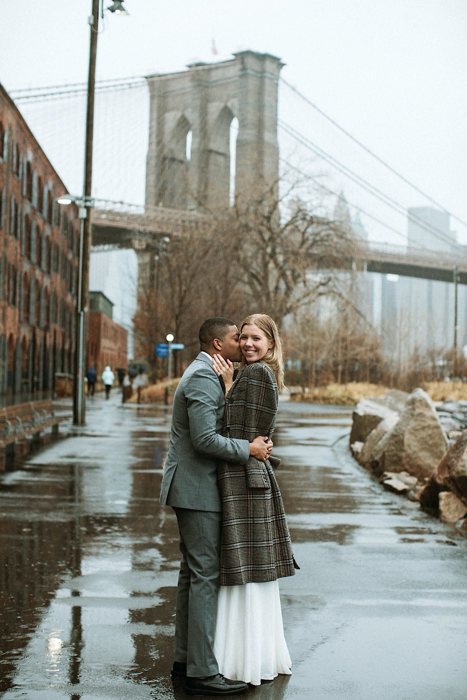 DUMBO Wedding Photography - Groom kisses bride on the cheek with Brooklyn Bridge in the Background