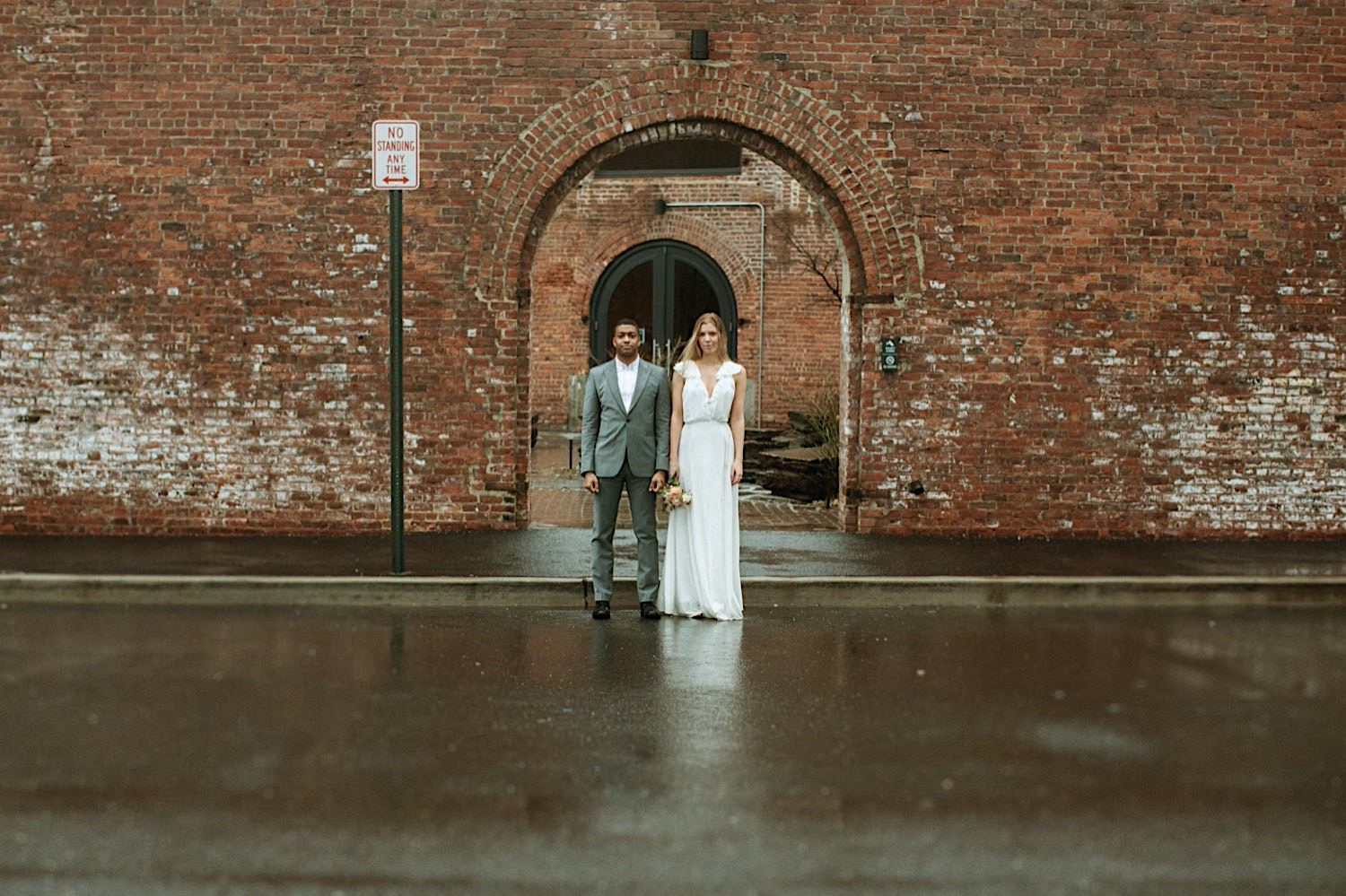 DUMBO Wedding Photography - A couple stands straight on looking at the camera with St. Ann's warehouse in the background in DUMBO