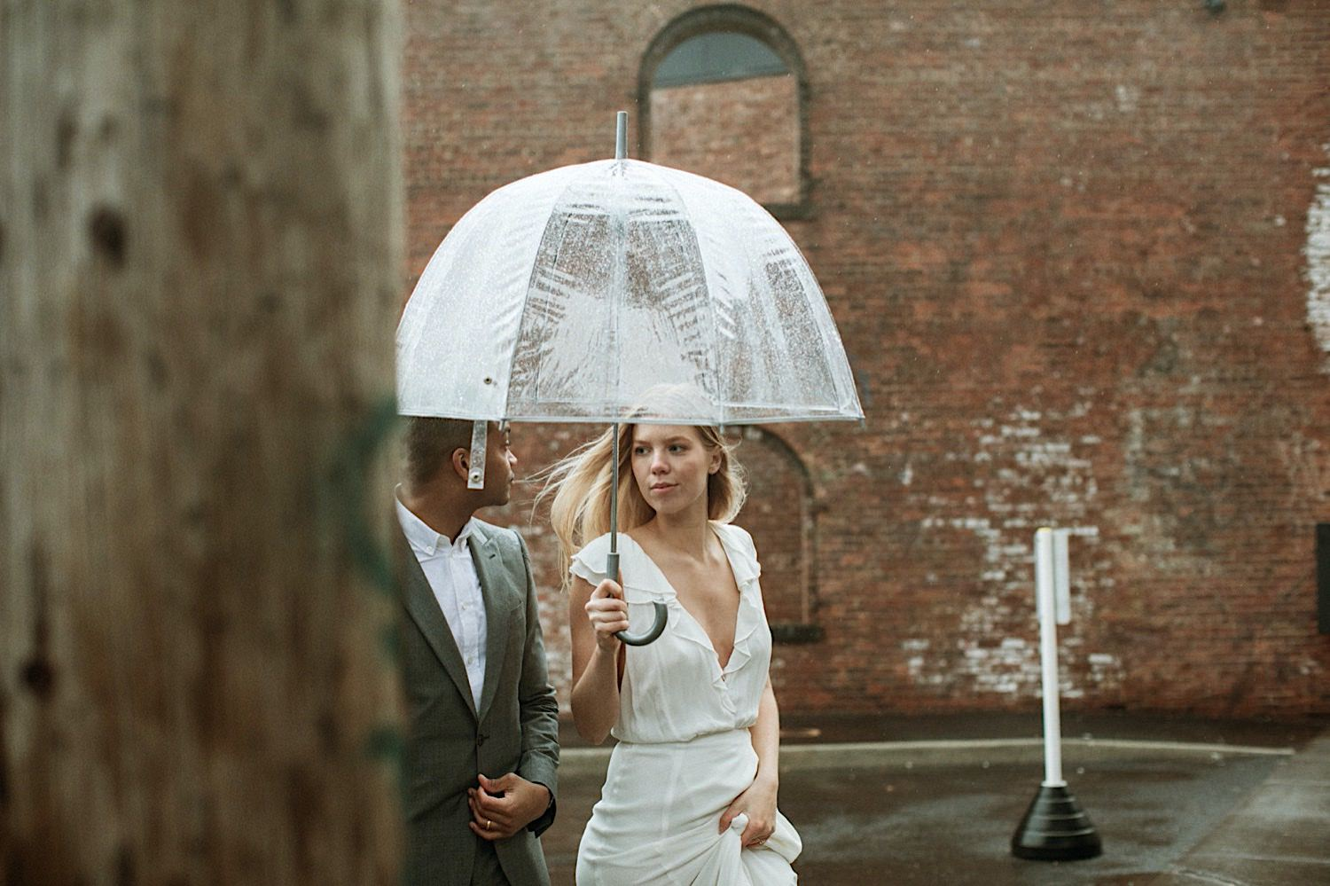 DUMBO Wedding Photography - Wedding Bride and Groom walk candidly under and umbrella in DUMBO NYC