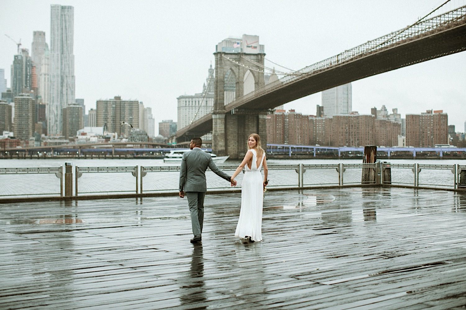 DUMBO Wedding - Bride in sleeveless dress leads groom on the pier in DUMBO Brooklyn facing the Brooklyn Bridge