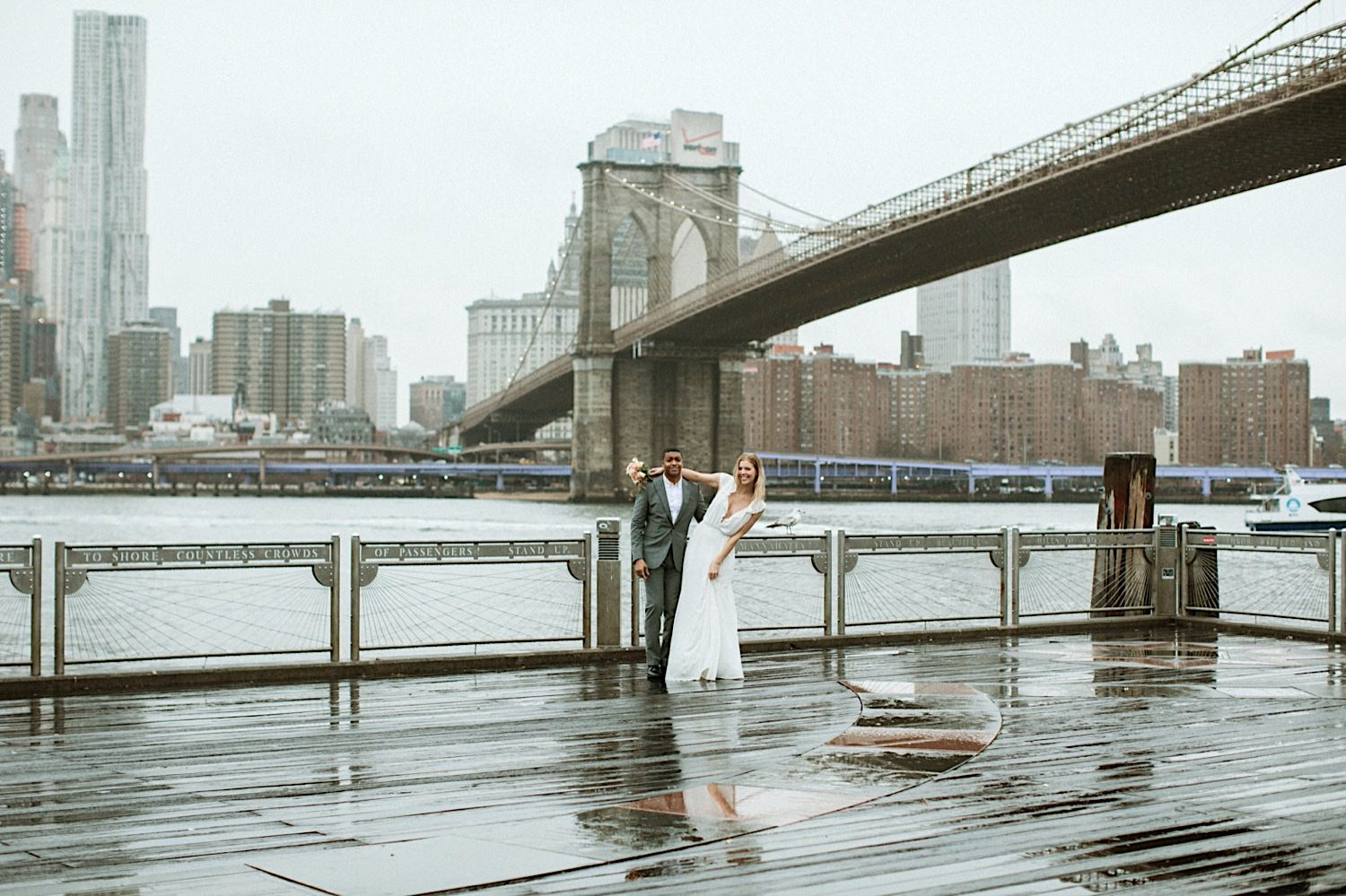 DUMBO Wedding Photography - Bride and Groom pose on the pier on a rainy day with the Brooklyn Bridge in the background