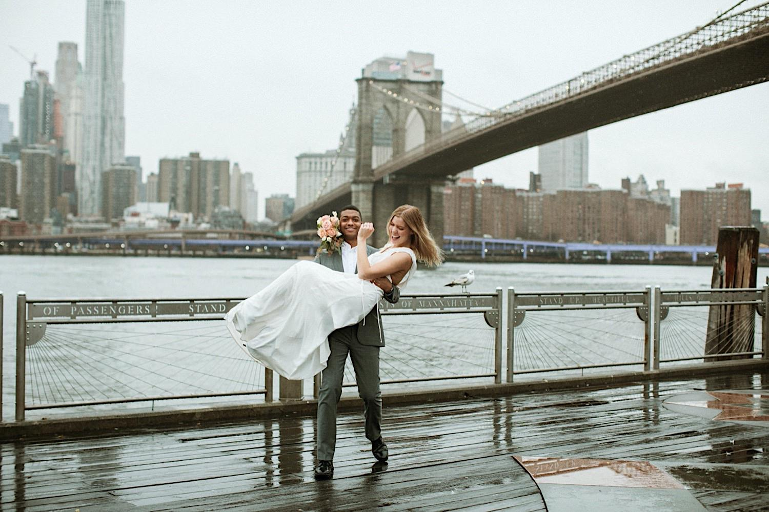DUMBO Wedding - Groom carries bride on pier with the Brooklyn Bridge as backdrop