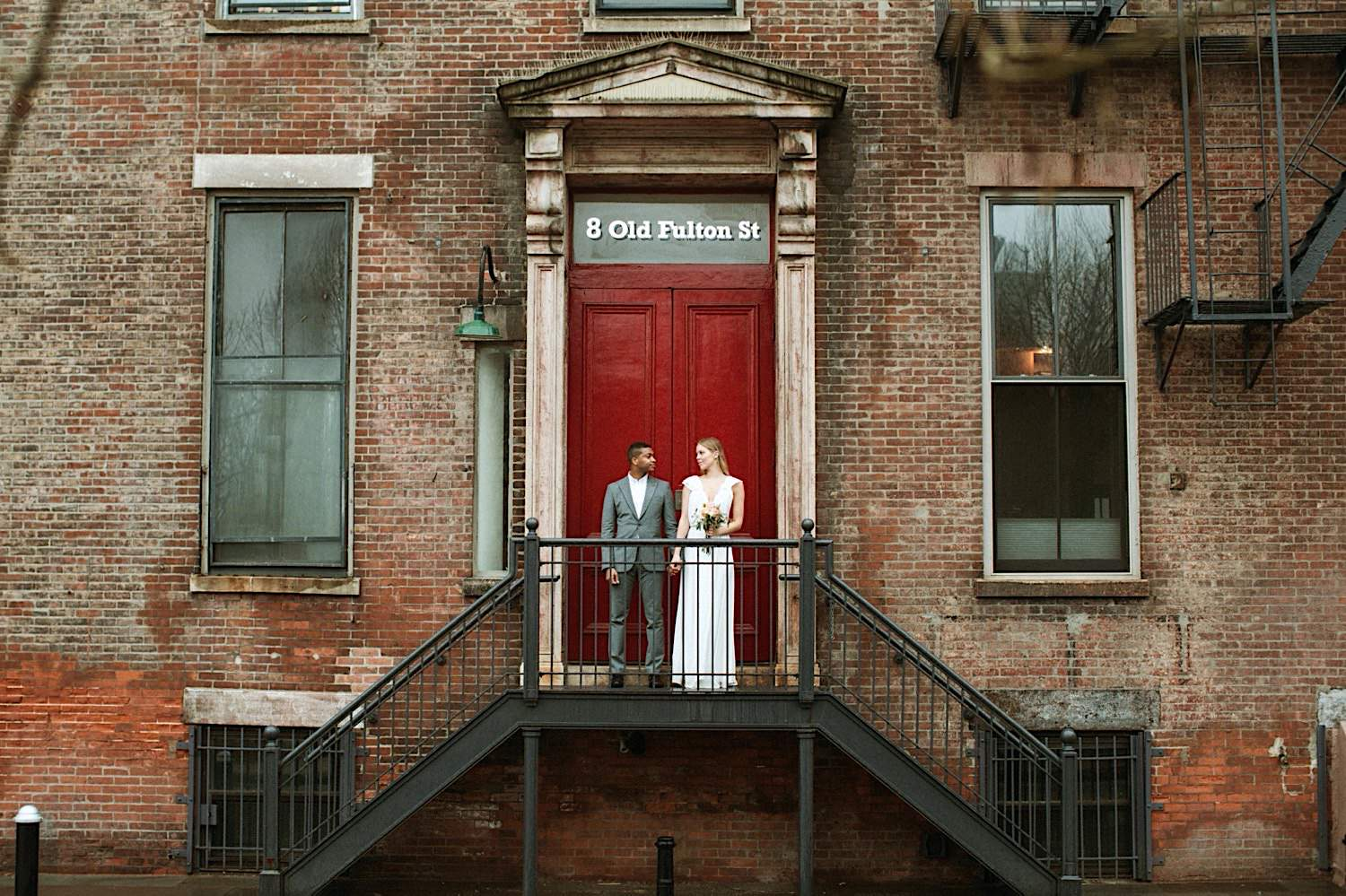 DUMBO Wedding Photography - A Wedding Couple Poses on the stairwell by a red door on Fulton Street in DUMBO Brooklyn