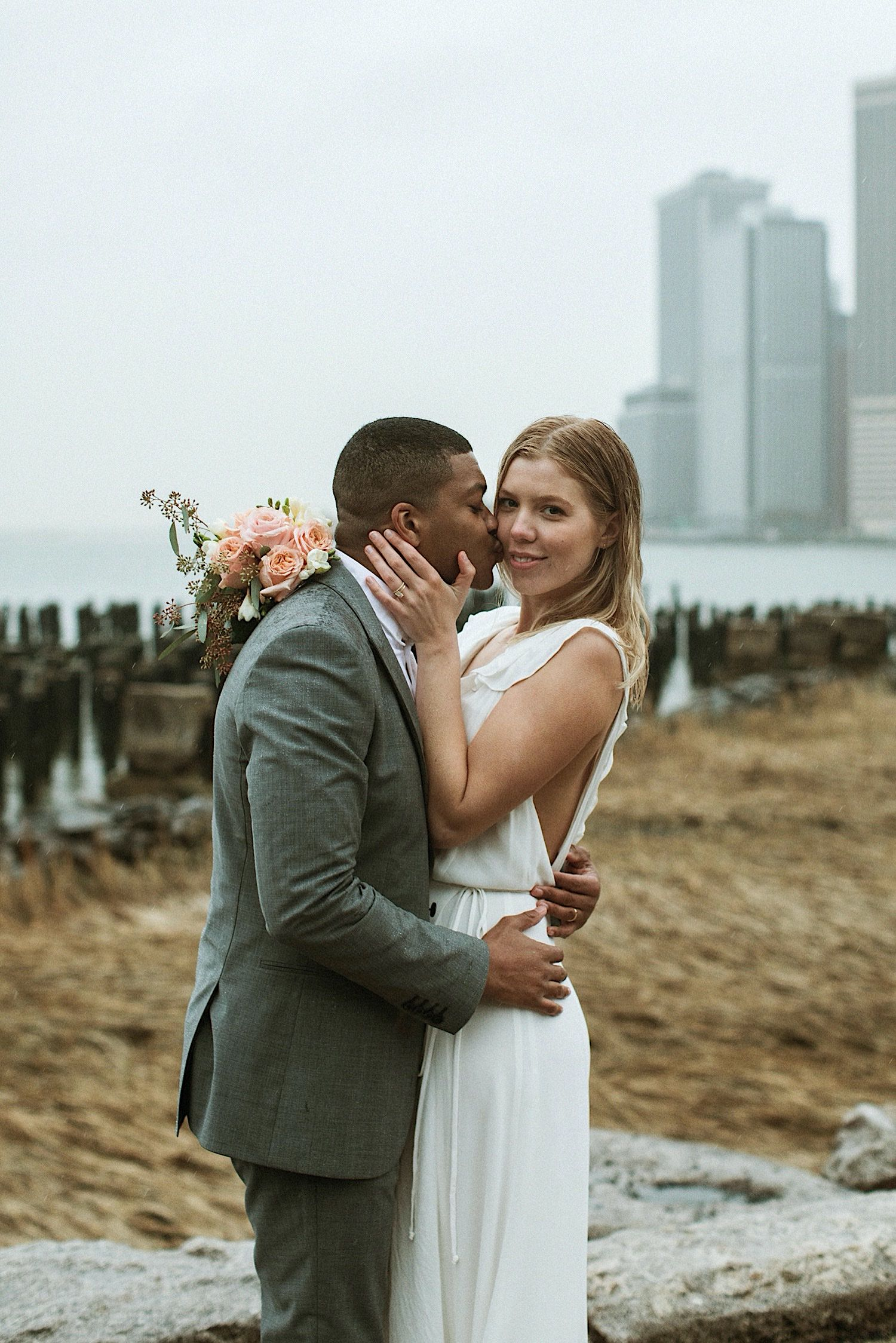 DUMBO Wedding Photography - Groom gives bride a kiss on the cheek as she smiles at the camera in DUMBO Brooklyn