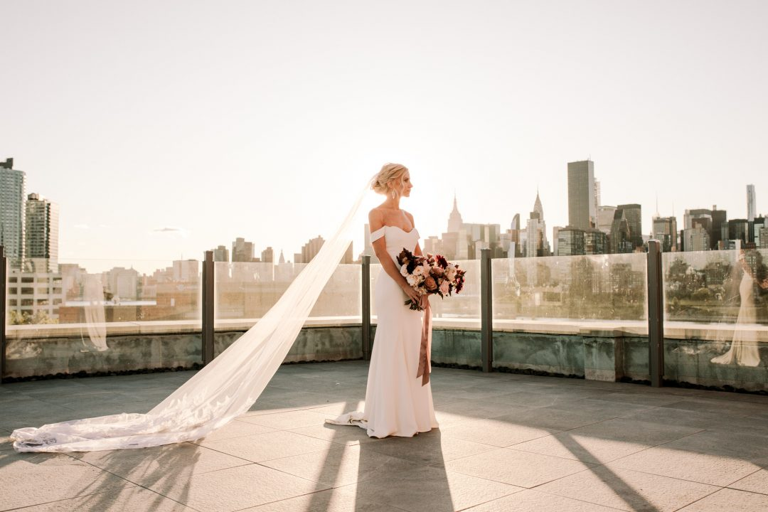 Minimony and microwedding at the Bordone LIC in New York. A bride stands with bouquet at Sunset