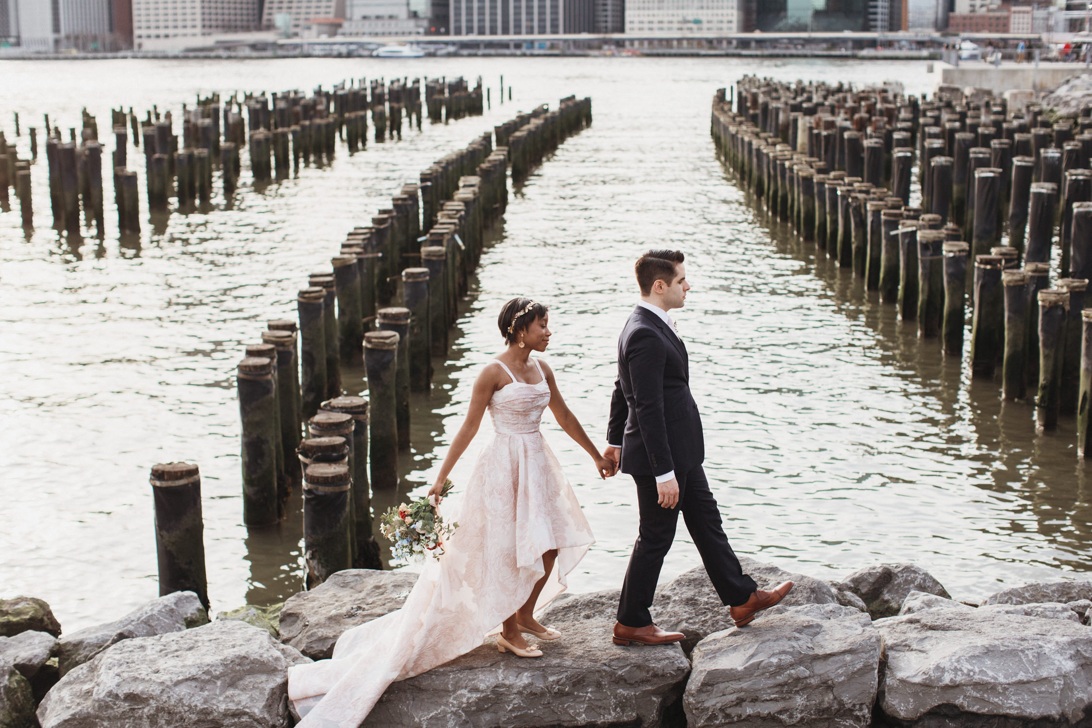 Couple walks on the rocks by the dock in DUMBO Brooklyn for Wedding Photos