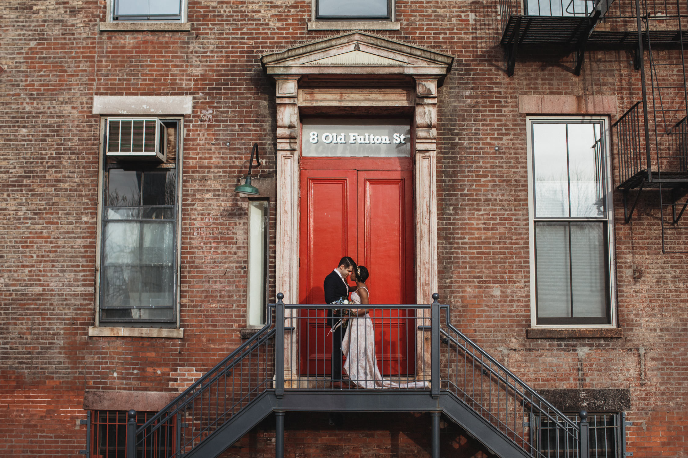 Wedding couple pose by a red door for wedding photos in DUMBO Brooklyn