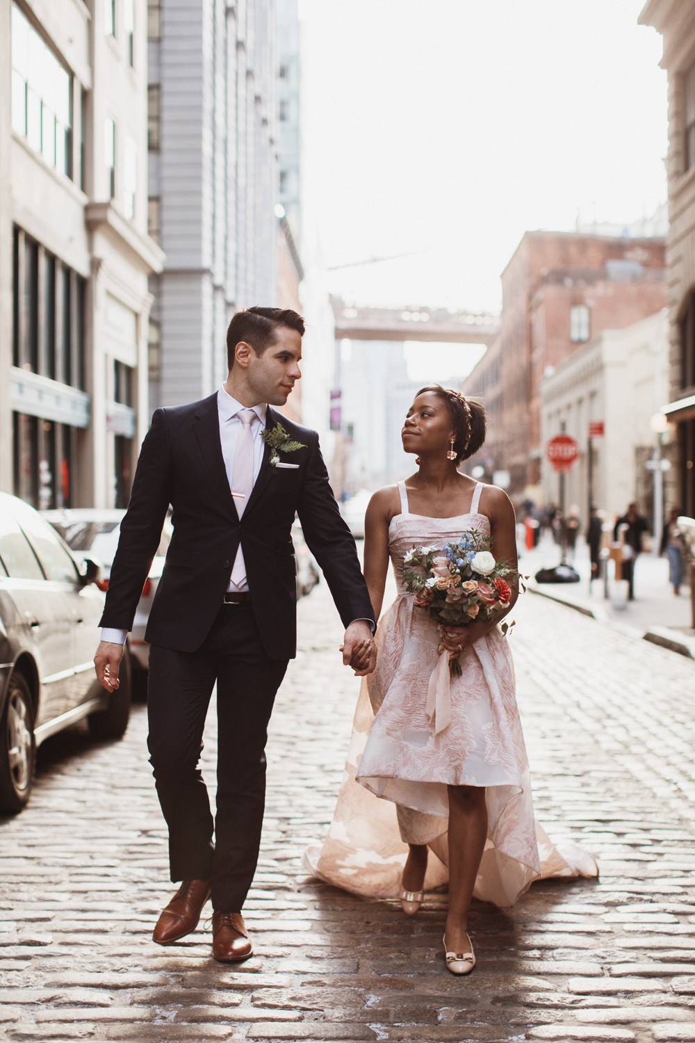 Couple walks down stone streets hand in hand for wedding photos in DUMBO Brooklyn