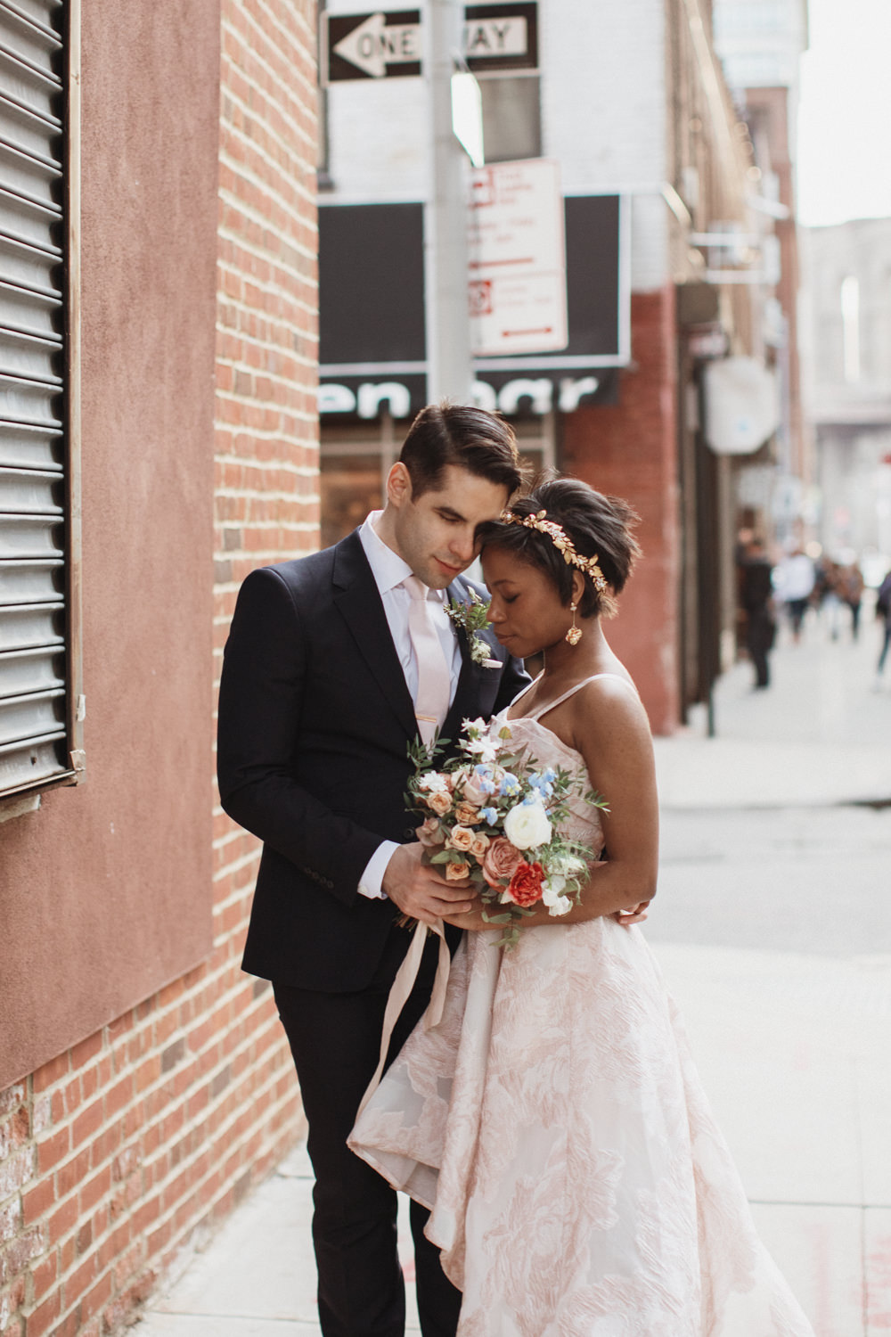 Couple poses for Wedding Photos by a brick wall in DUMBO Brooklyn