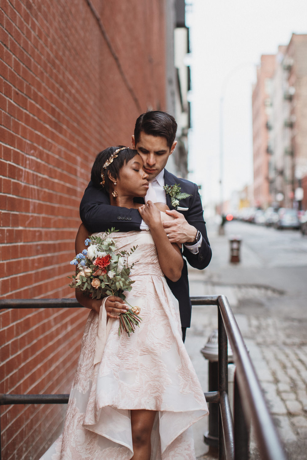Man holds his wife in wedding photos in DUMBO Brooklyn